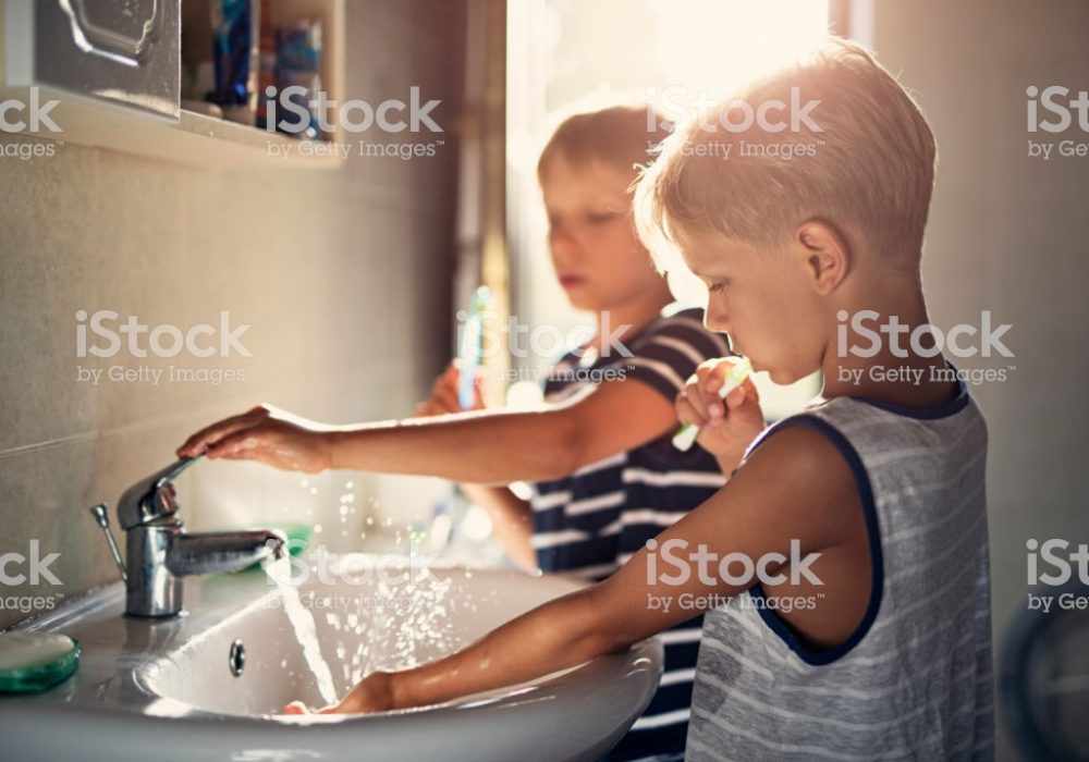 Two boys aged 8 are brushing teeth together in a bathroom.